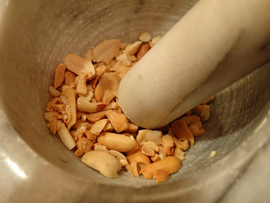 Crush peanuts in mortar and pestle